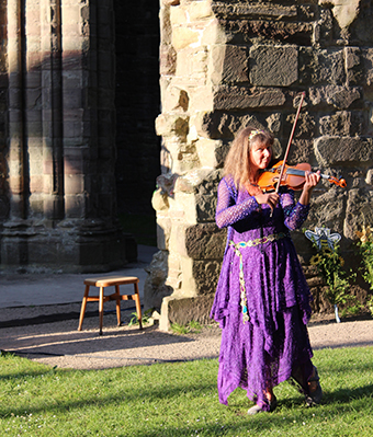 Fiona playing the violin in Tintern abbey
